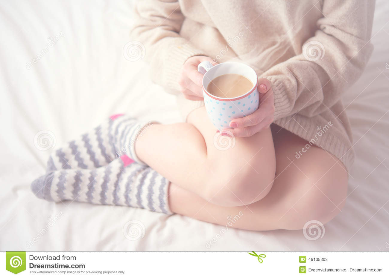 Legs of girl warm woolen socks and cup of coffee warming, winter morning in bed