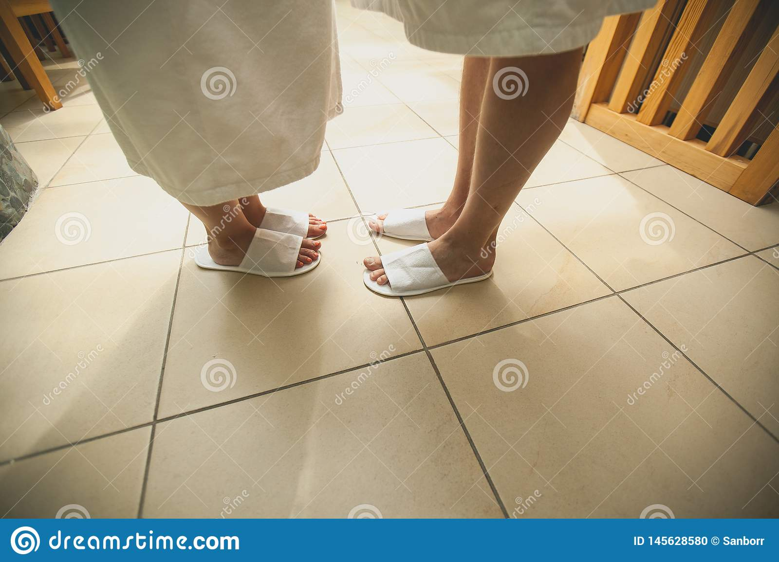 Legs of a man and a woman in swimming Slippers close-up. Young couple in bath robes and Slippers, standing on the tiled floor