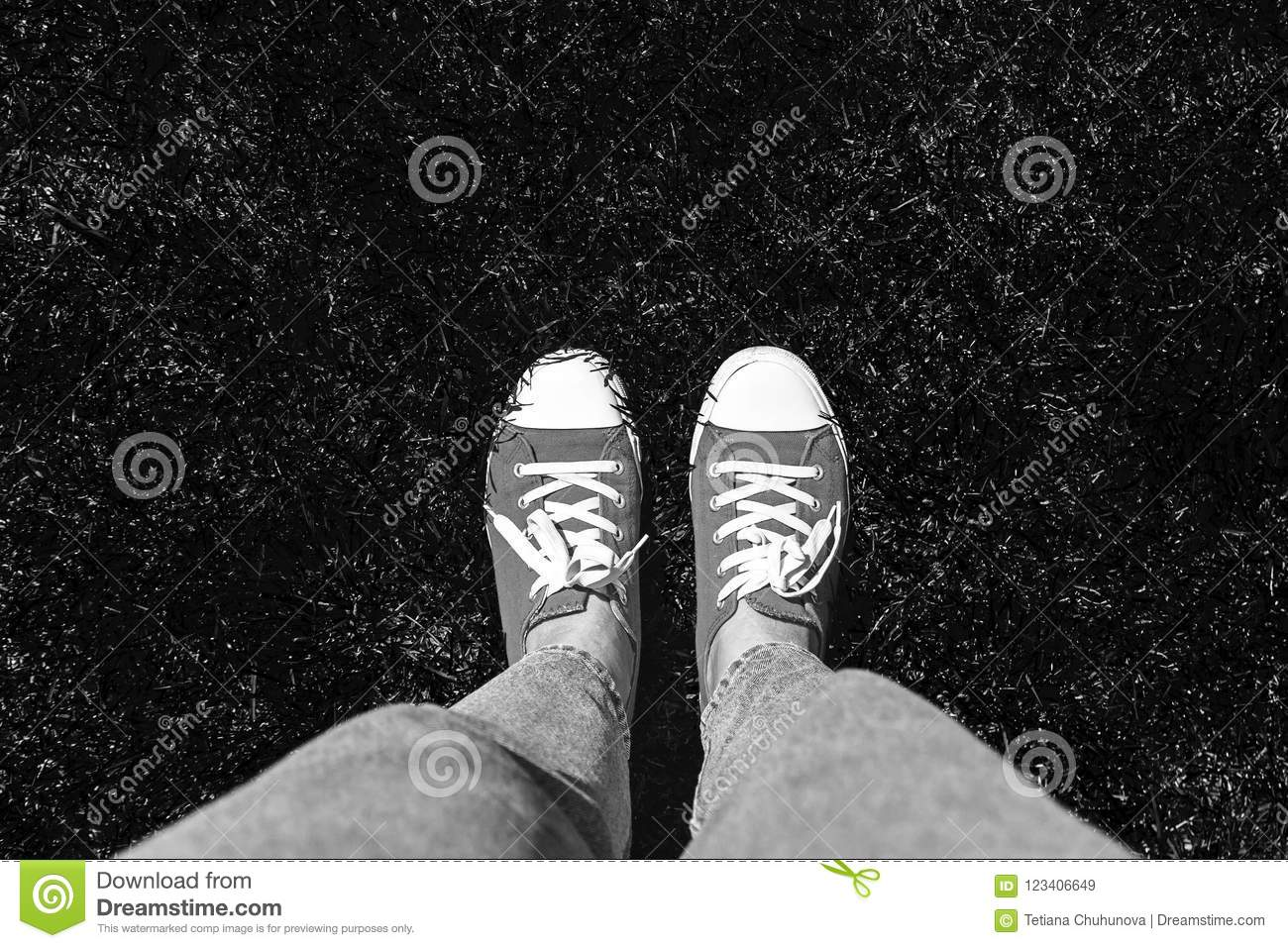 Legs in old sneakers on grass. View from above. Style: abstraction, illustration, monochrome, neon