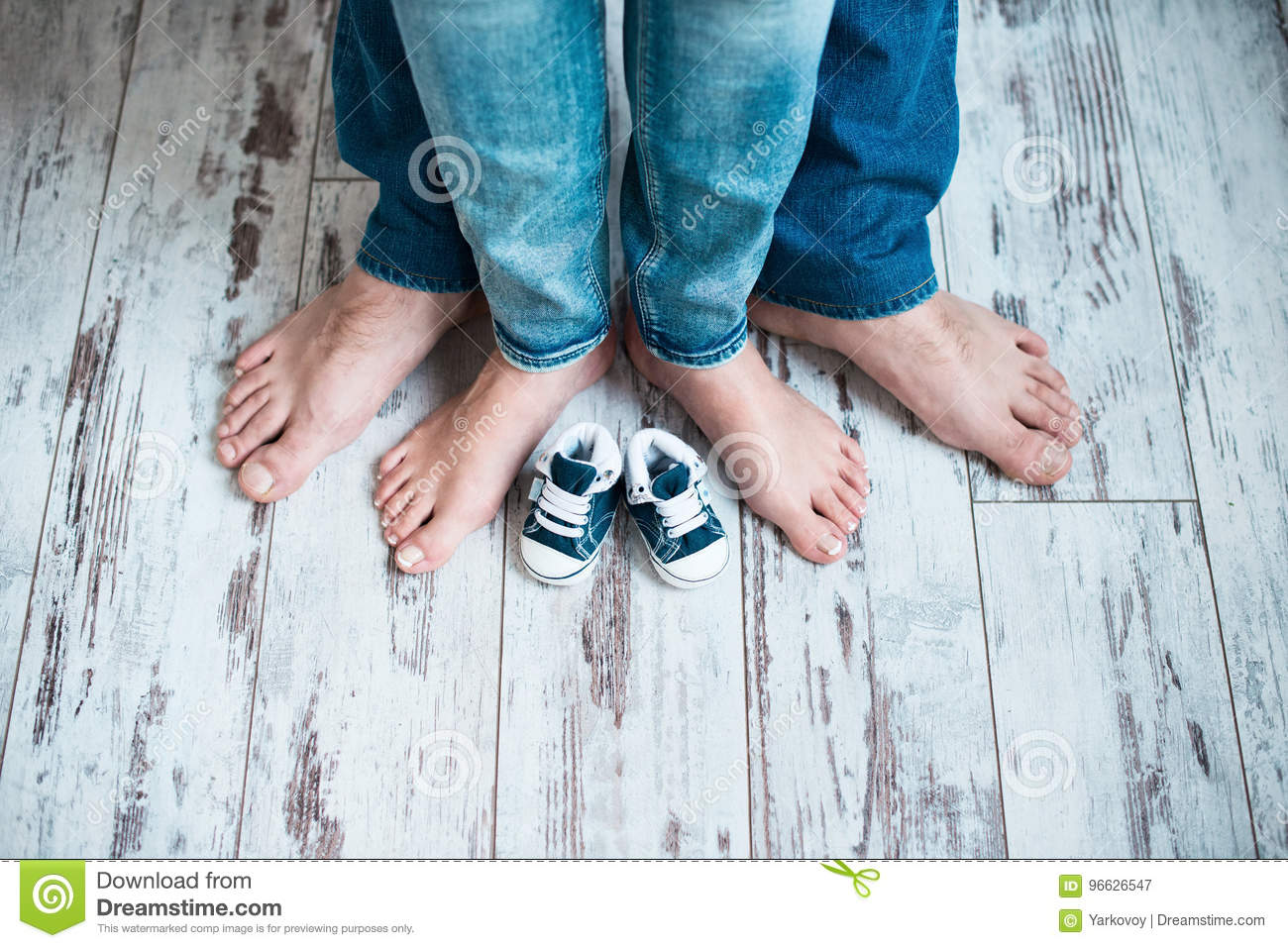 c6a8ca845260 Legs Of Parents With Children`s Sneakers. Waiting For The Baby ...
