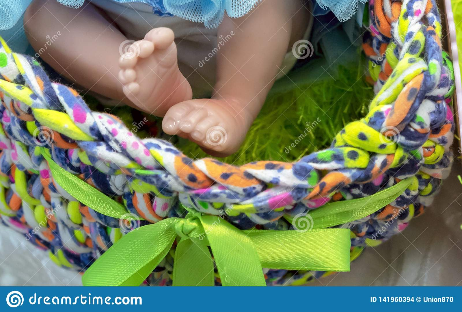 Legs of a realistic baby doll in a multi-colored basket
