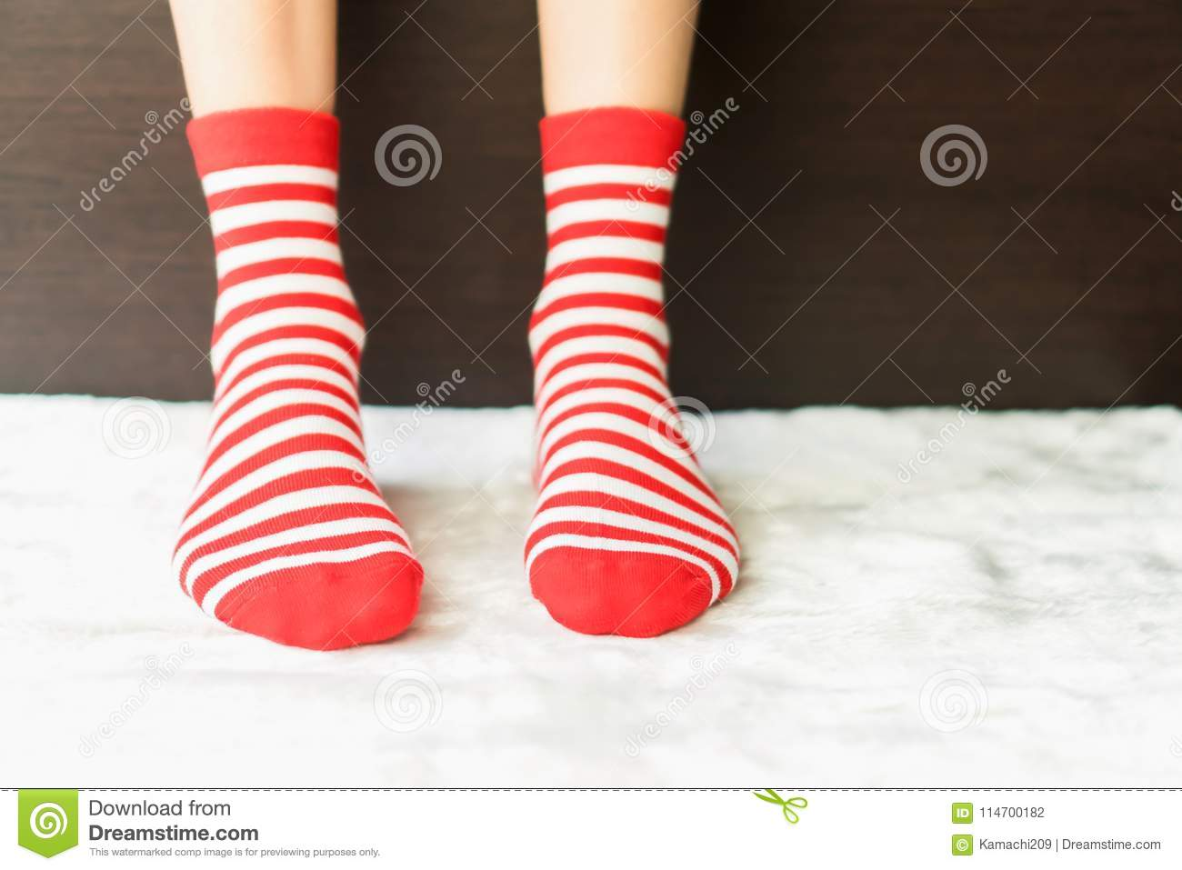Legs in socks red colors alternate, white side stand on white fabric floor.