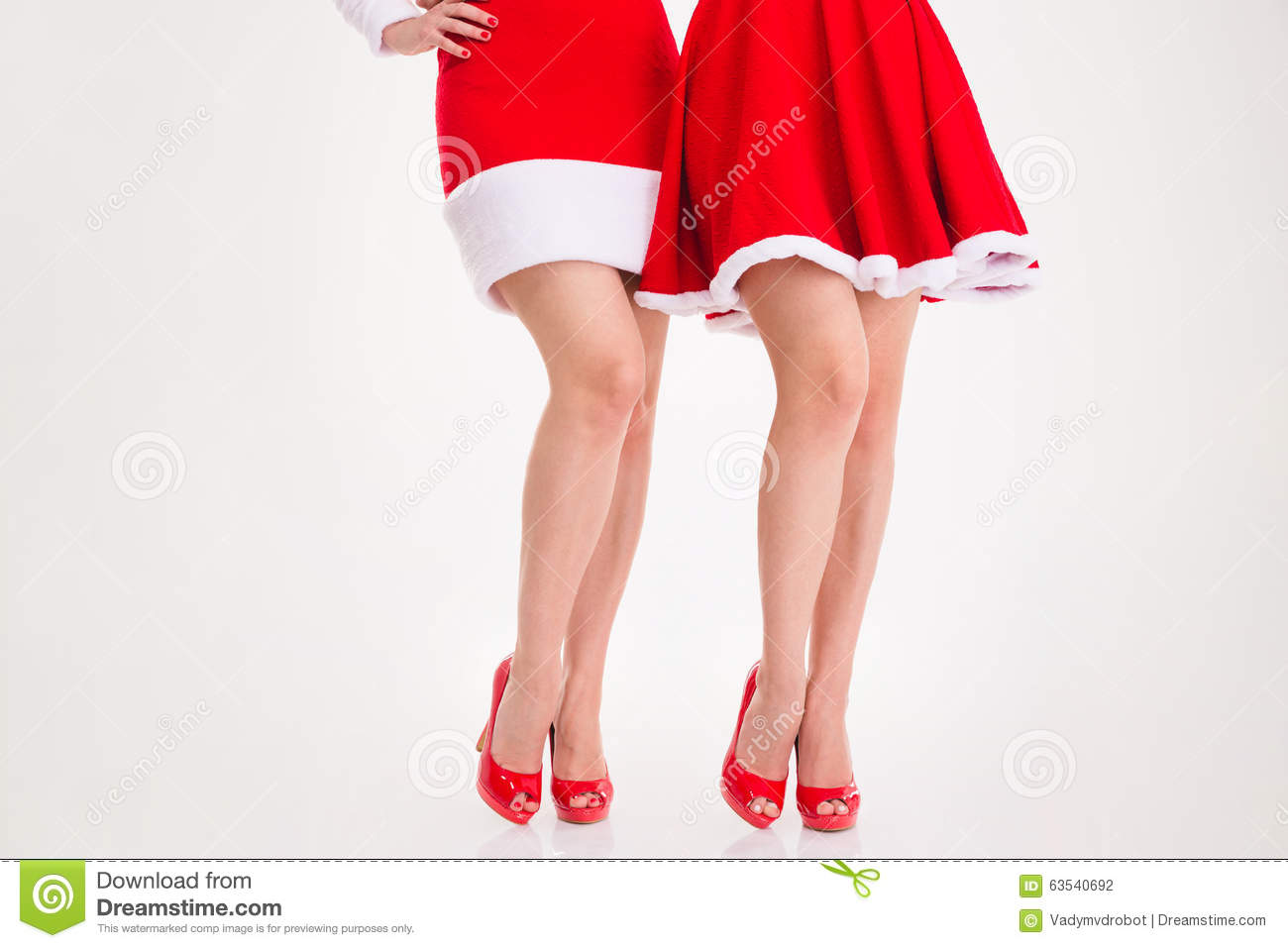 Beautiful legs of two young women in santa claus dresses and red shoes over  white background c36104d0e8