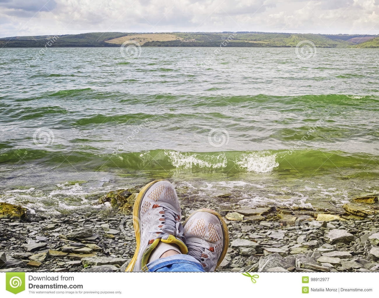 91356a90afb2 Legs Of A Woman In Sneakers Relaxing On The Rocky Beach Stock Image ...
