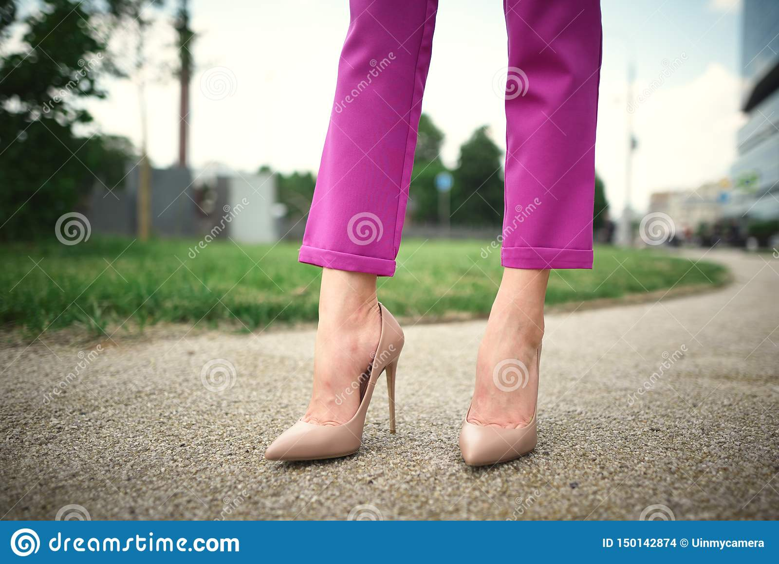 legs of a young girl in heels stand on the street