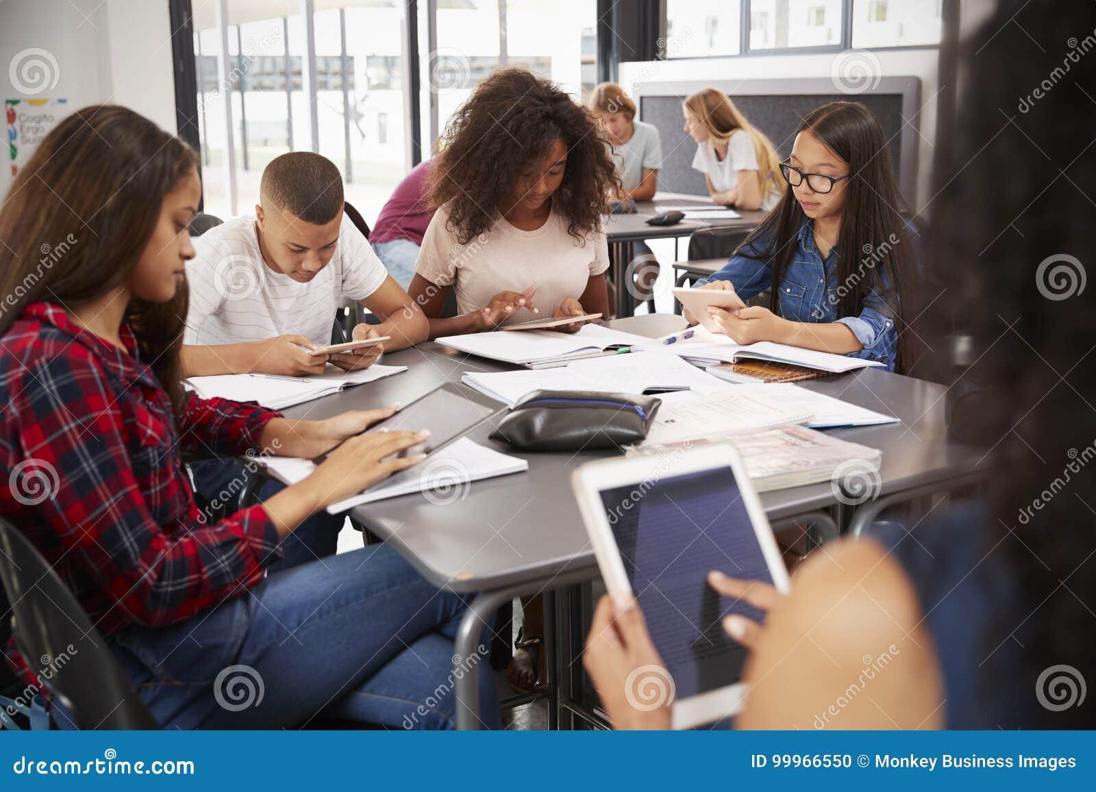 Lehrer, der mit den hohen Schülern verwenden Tabletten sitzt