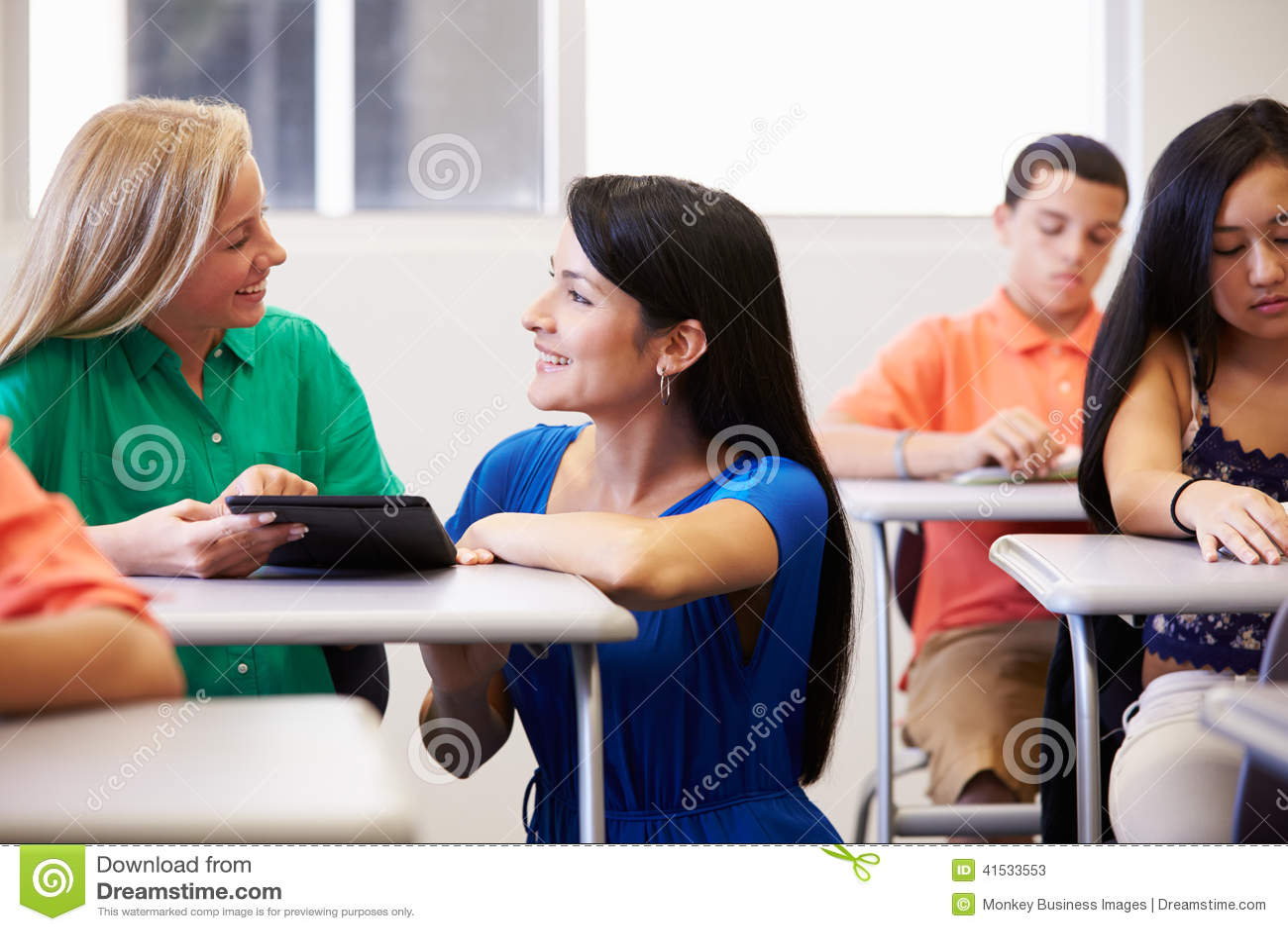 Lehrer-Helping Female High-Schüler In Classroom