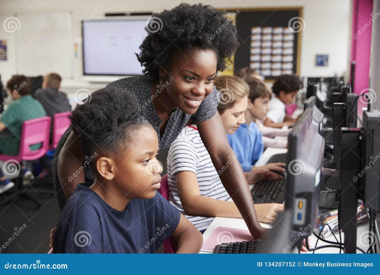 Lehrer-Helping Female Pupil-Linie von den hohen Schülern, die an den Schirmen in der Computer-Klasse arbeiten