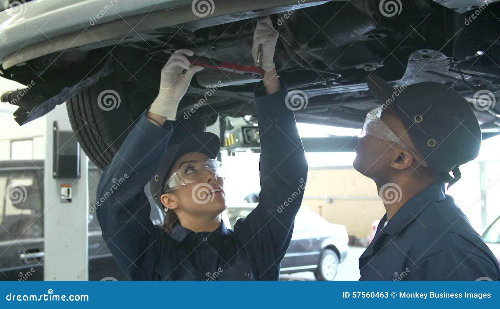 Lehrer Helping Female Student, Das Ausbildet, Um Auto-Mechaniker Zu ...