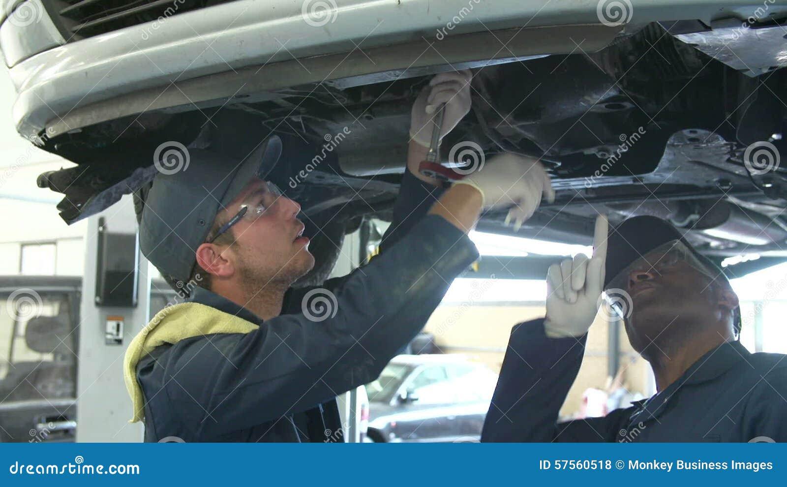 Lehrer Helping Male Student, Das Ausbildet, Um Auto-Mechaniker Zu ...