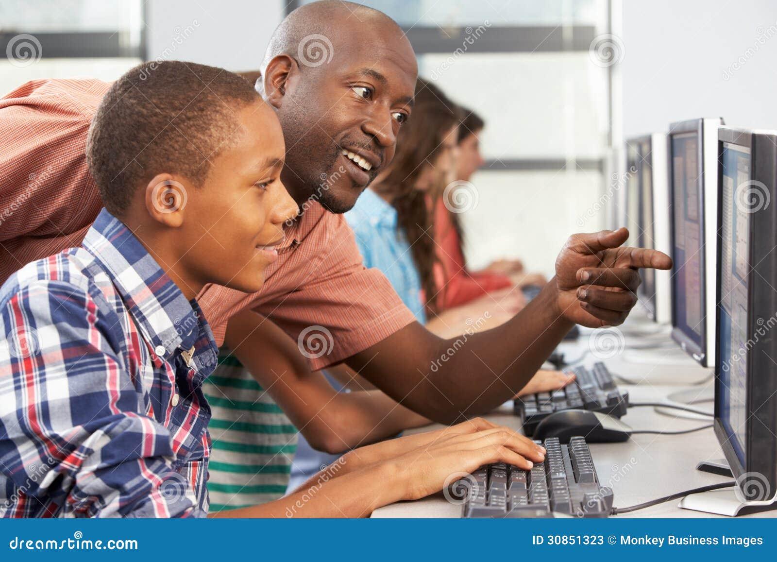 Lehrer Helping Students Working an den Computern im Klassenzimmer