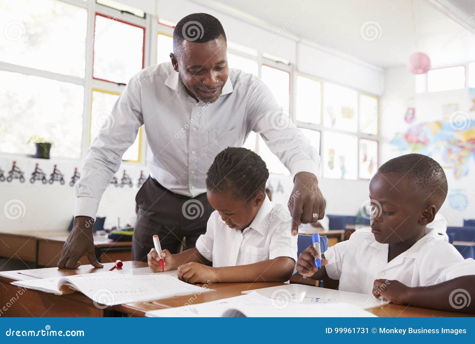 Lehrer steht helfende Volksschulekinder an ihren Schreibtischen