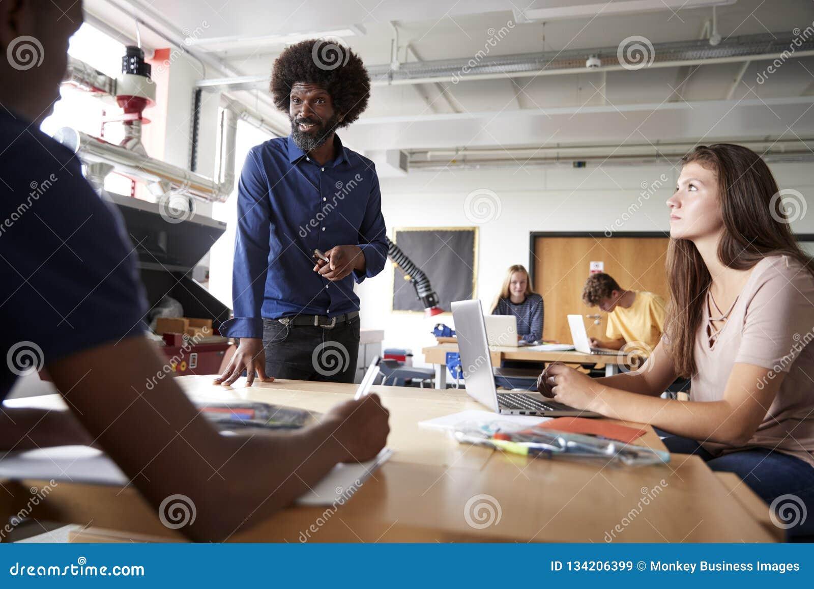 Lehrer Talking To Group von den hohen Schülern, die an den Werkbänken in der Entwurfs-und Technologie-Lektion sitzen
