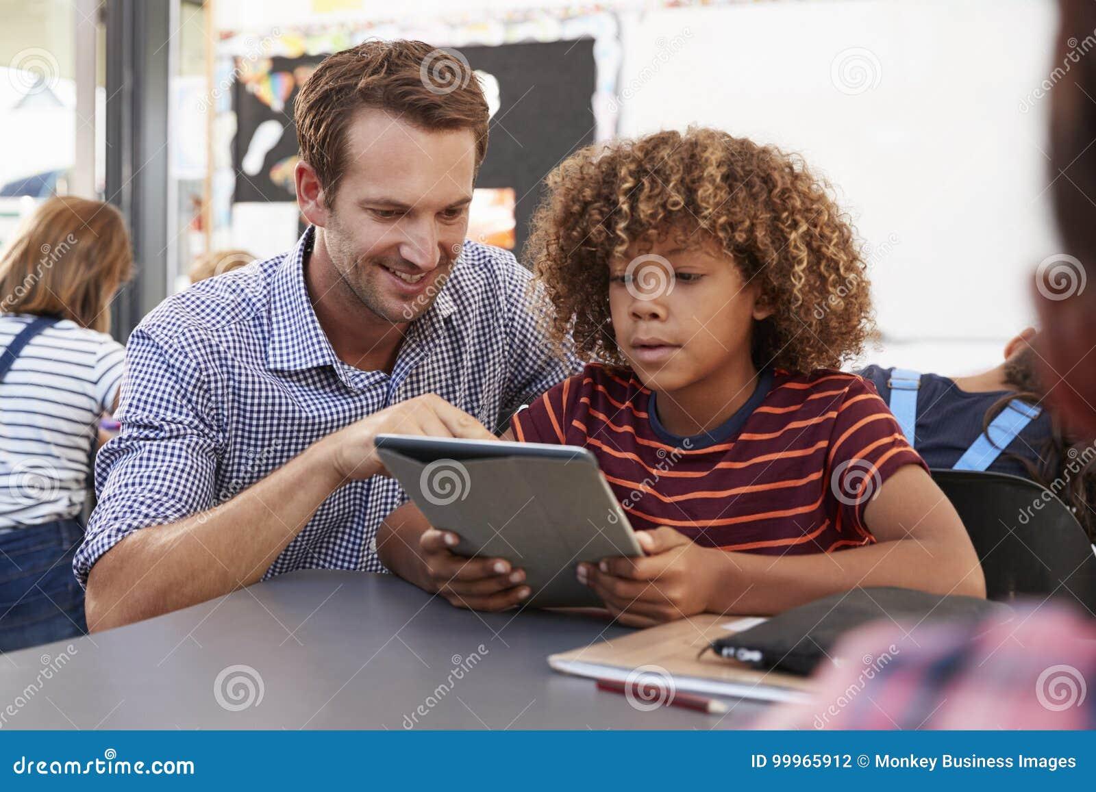 Lehrer und Schüler, der Tablet-Computer in der Klasse verwendet