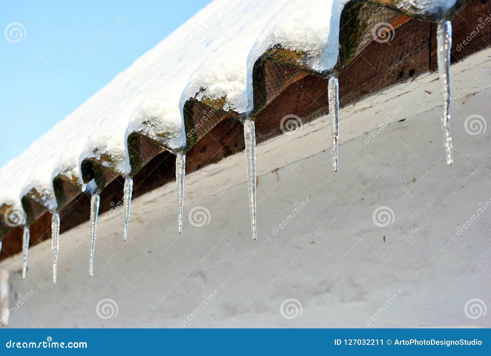 Leidaken met ijskegels met sneeuw worden behandeld, met sneeuw wordt behandeld, witte muurachtergrond die