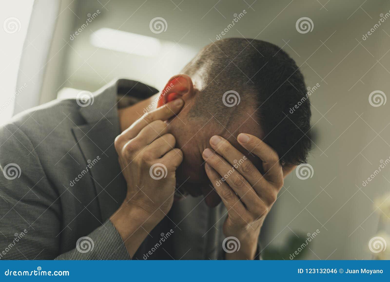 Leidender Mann mit seinen Händen in seinem Kopf