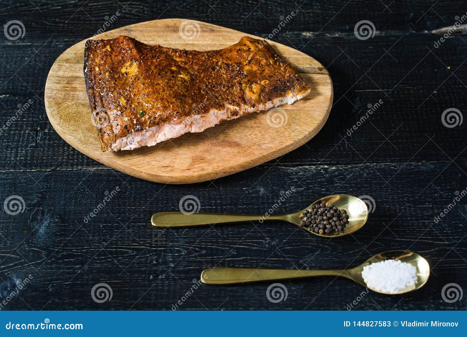 Leiste des geräucherten Lachses auf schwarzem hölzernem Hintergrund