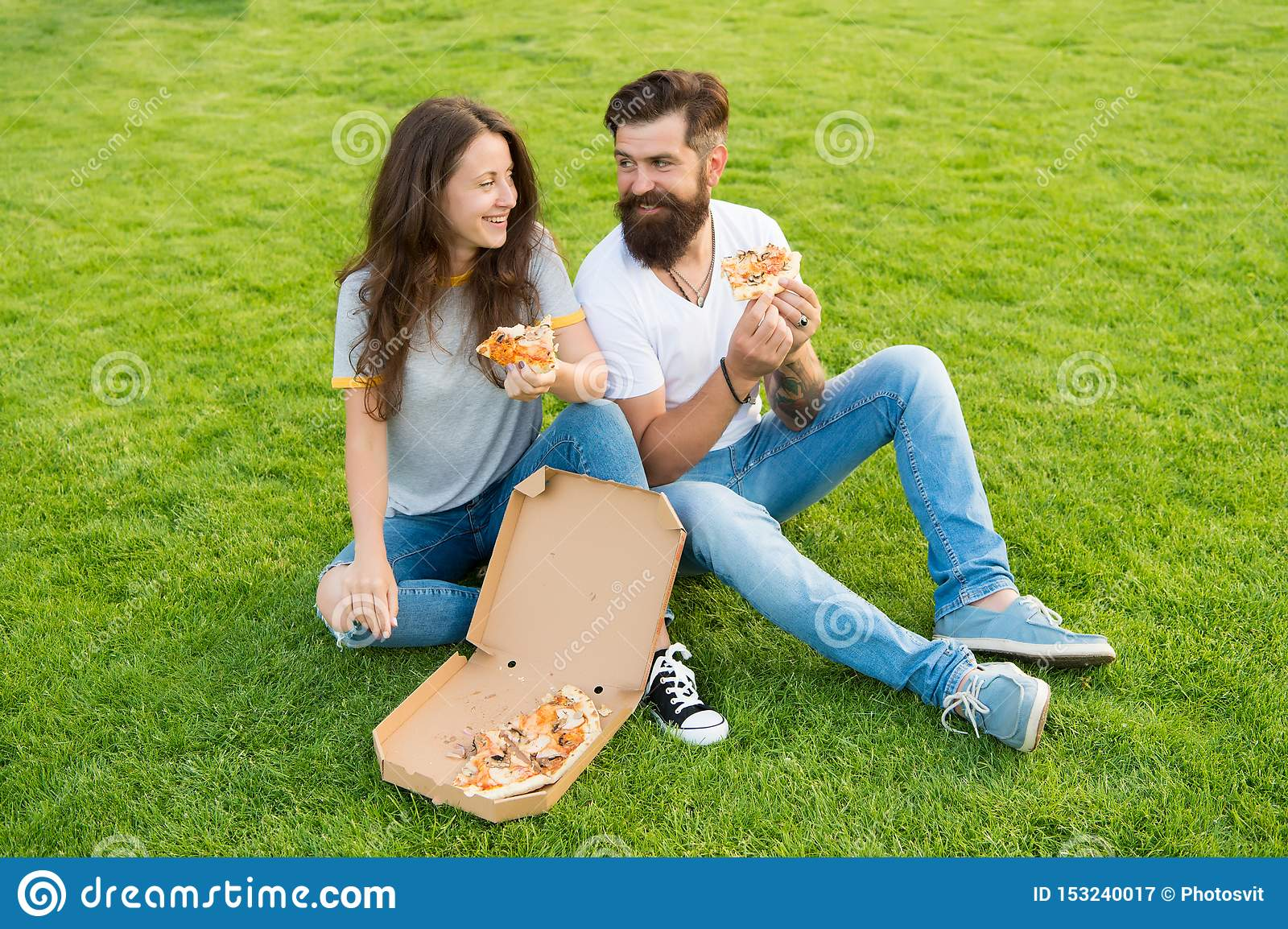 Leisure time. fast food. bearded man hipster and adorable girl eat pizza. summer picnic on green grass. Diet. couple in