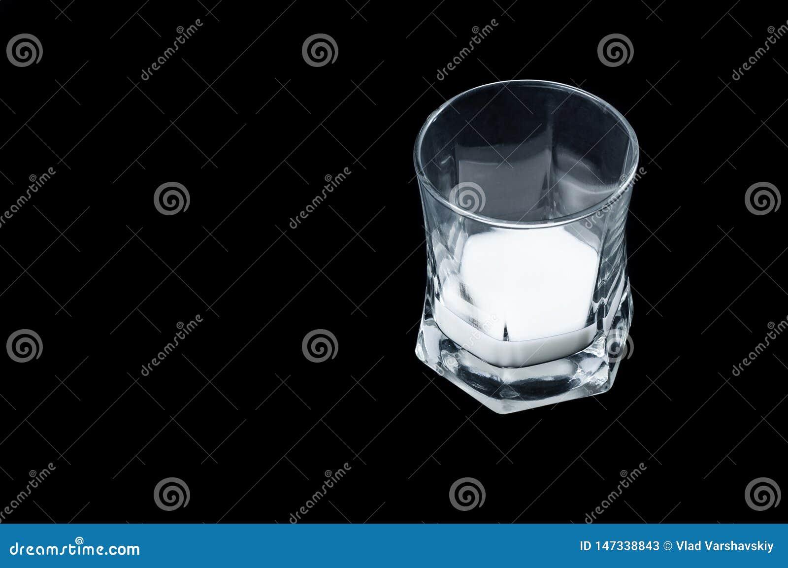 Leite branco em uma opinião lateral do vidro de vidro transparente em um fundo preto, isolado