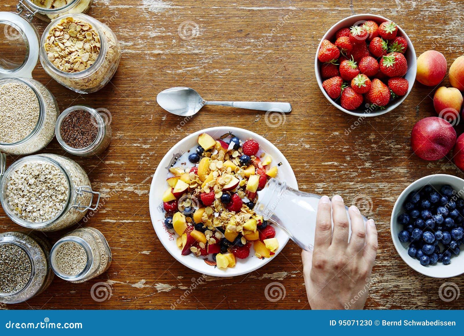 Leite de derramamento da mão da cena do café da manhã na nutrição orgânica do estilo de vida saudável do muesli