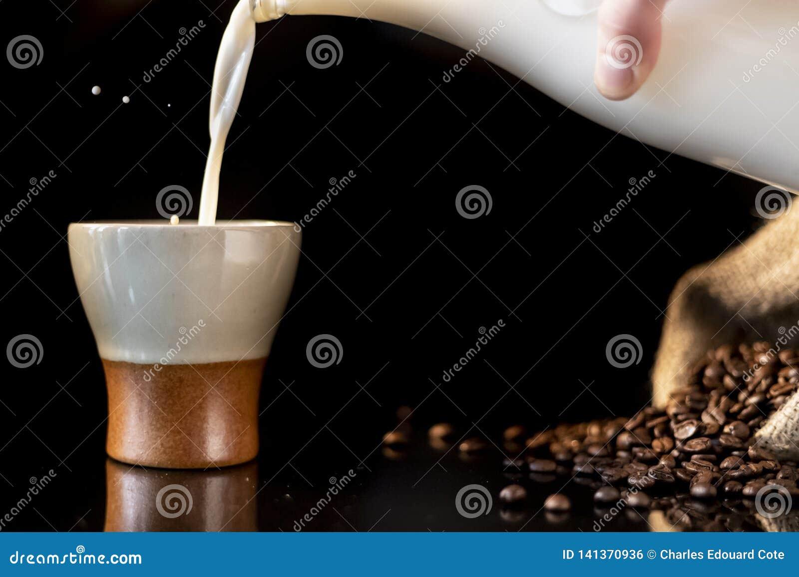 Leite de derramamento em uma xícara de café bonita com um respingo do leite