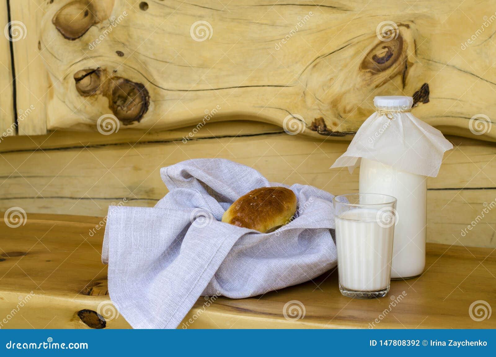 Leite fresco em uma garrafa de vidro e em um vidro, ao lado das tortas em uma tabela de madeira O conceito de produtos org?nicos