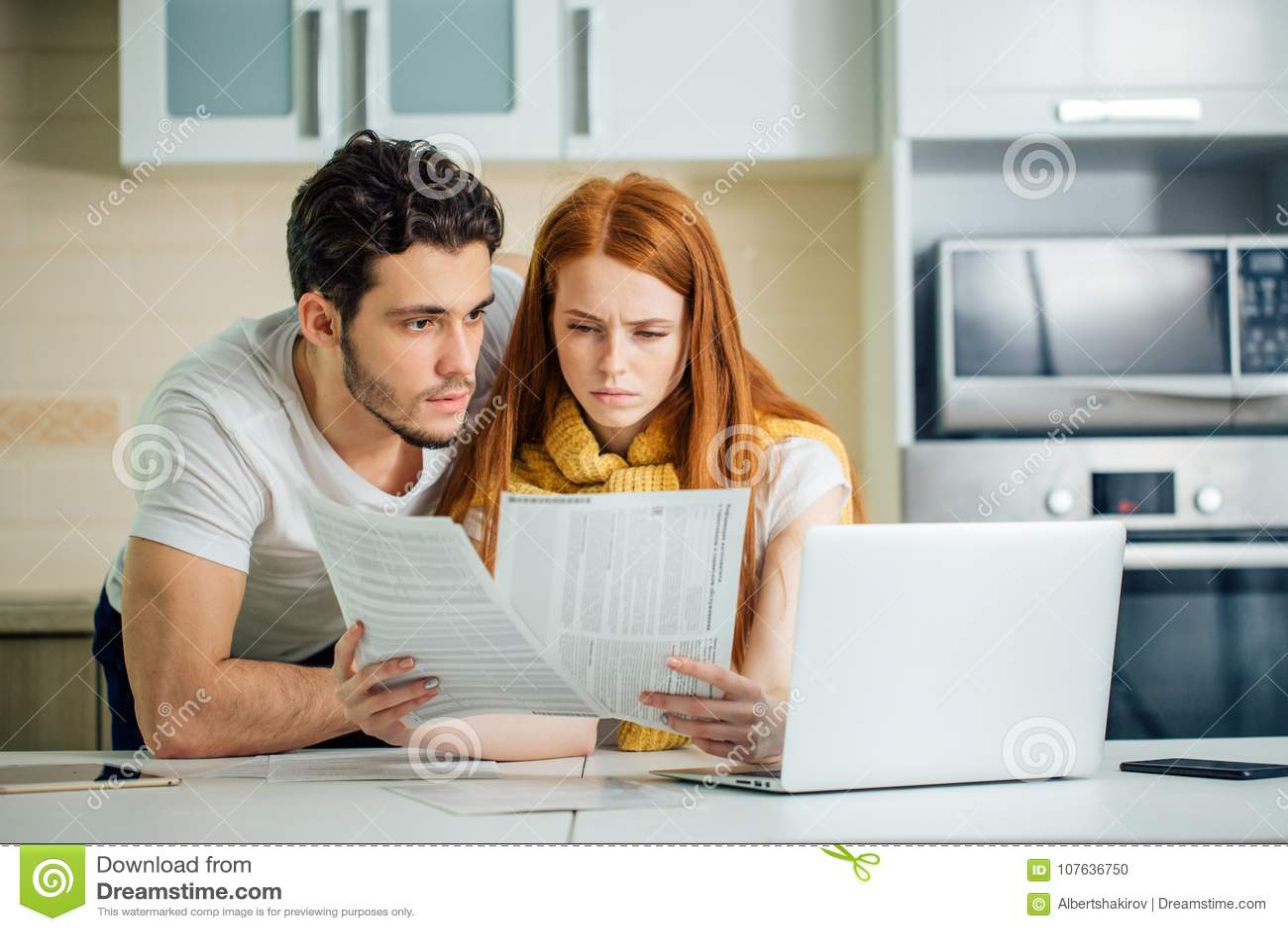 Leitungsbudget der Familie, ihre Bankkonten unter Verwendung des Laptops in der Küche wiederholend