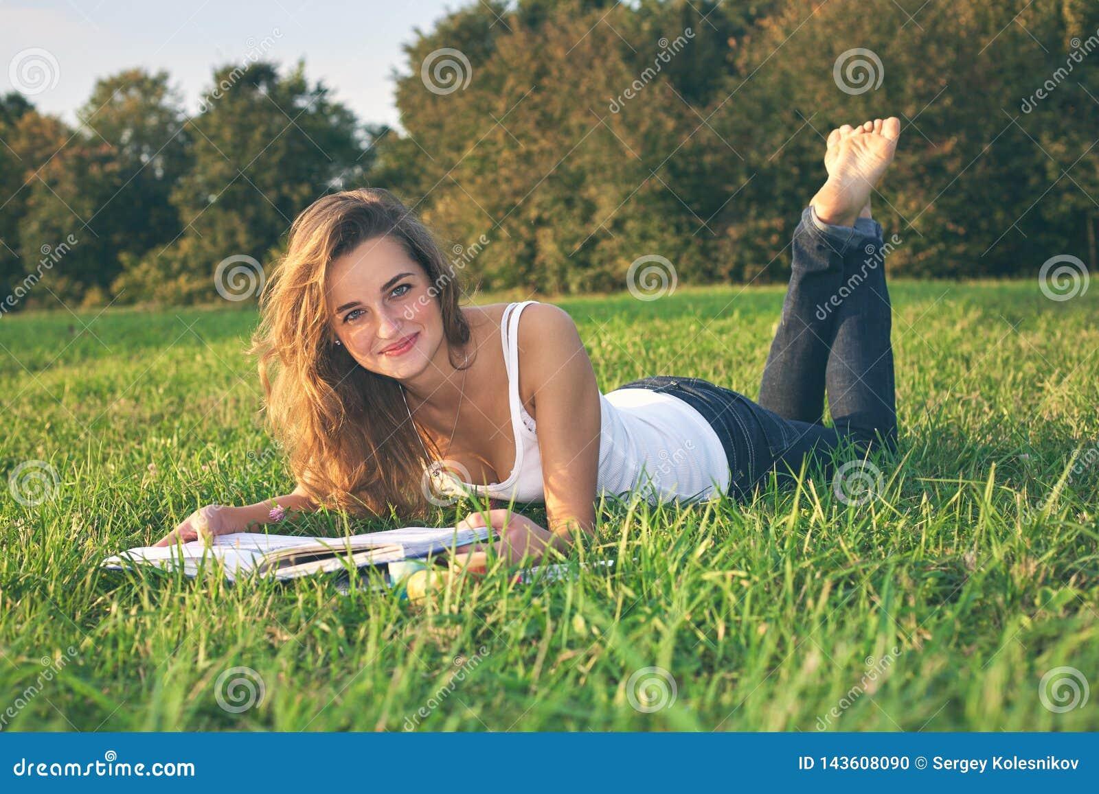 Leitura bonita da jovem mulher em um prado verde