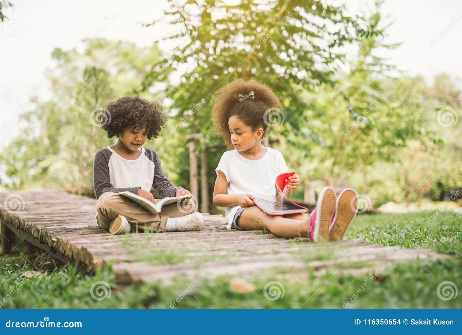 Leitura da criança pequena com amigo