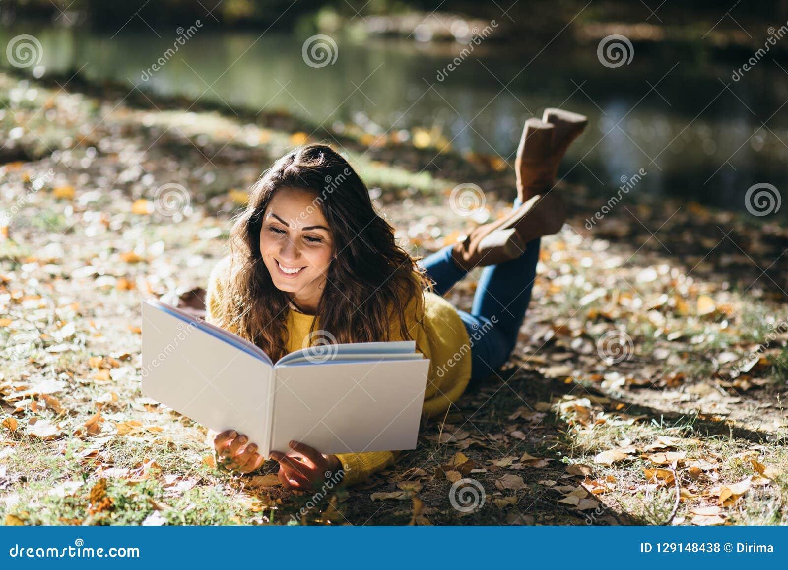 Leitura da mulher no outono exterior