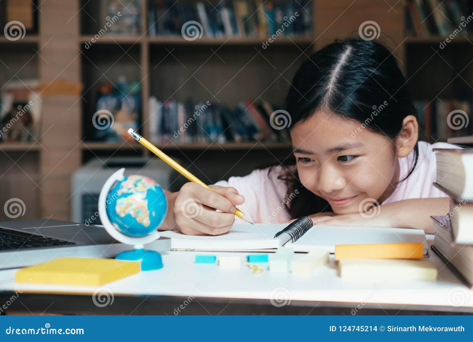 A leitura e a escrita da menina e fazem trabalhos de casa na biblioteca