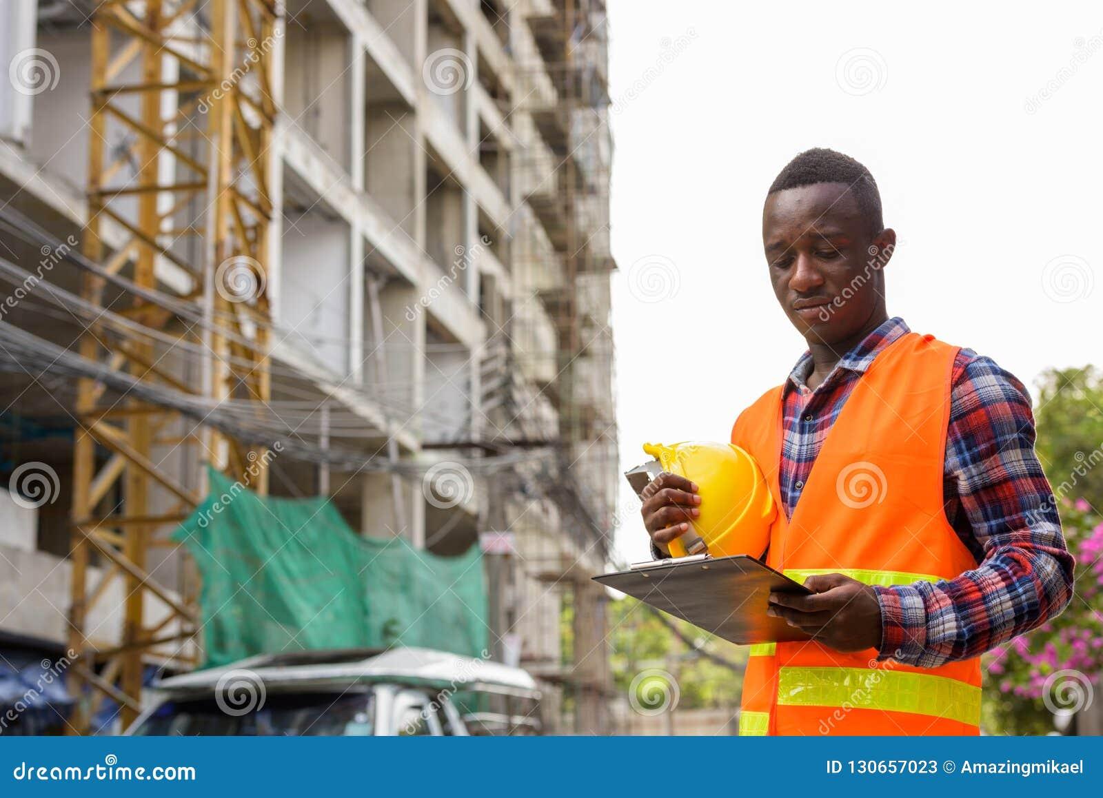 Leitura nova do trabalhador da construção do homem do africano negro na prancheta