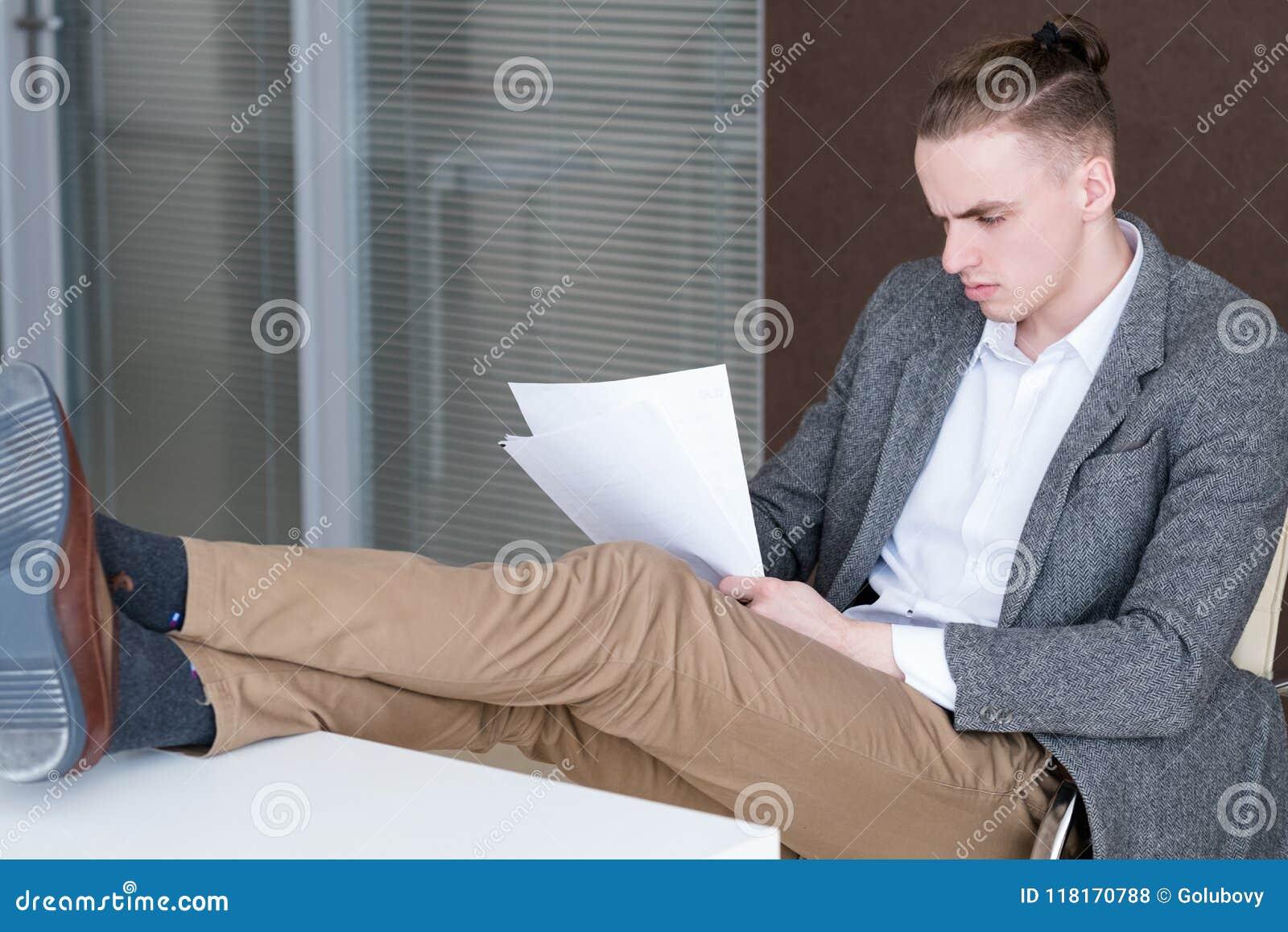 A leitura relaxado do diretor empresarial forra o escritório