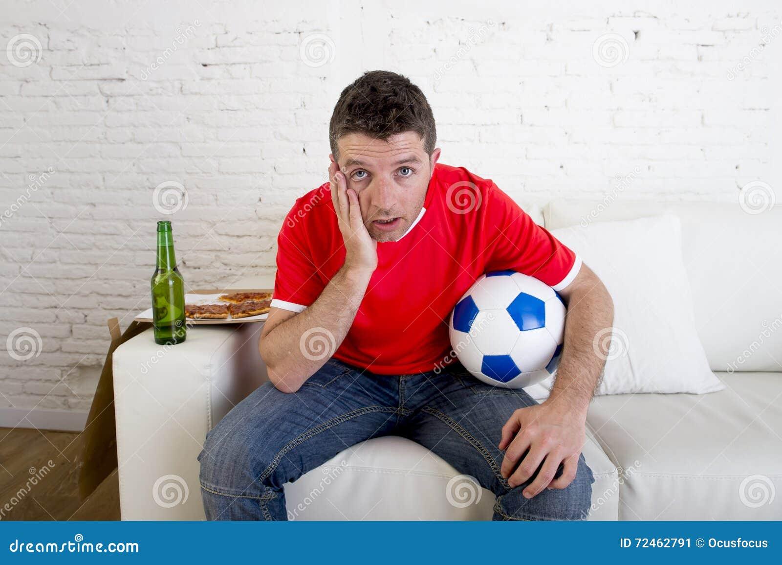 Lek för fotboll för man för ung fan hållande ögonen på på för lagärmlös tröja för television nervöst bärande lidande och spänning