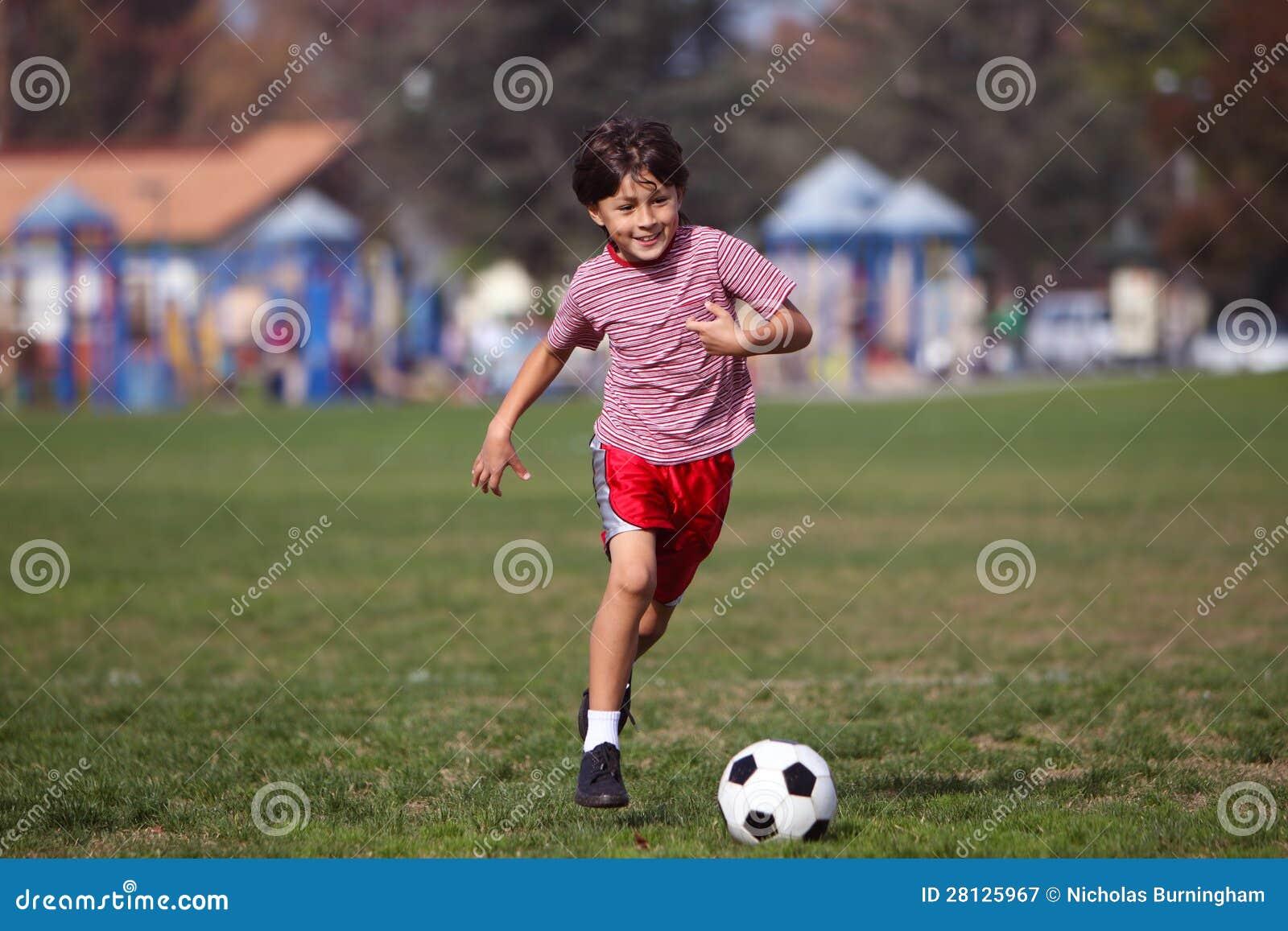 Leka fotboll för pojke i parkera