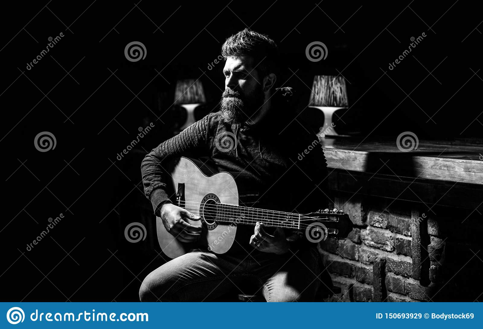 Leka gitarren Skägghipsterman som sitter i en bar Gitarrer och rader Uppsökt man som spelar gitarren som rymmer