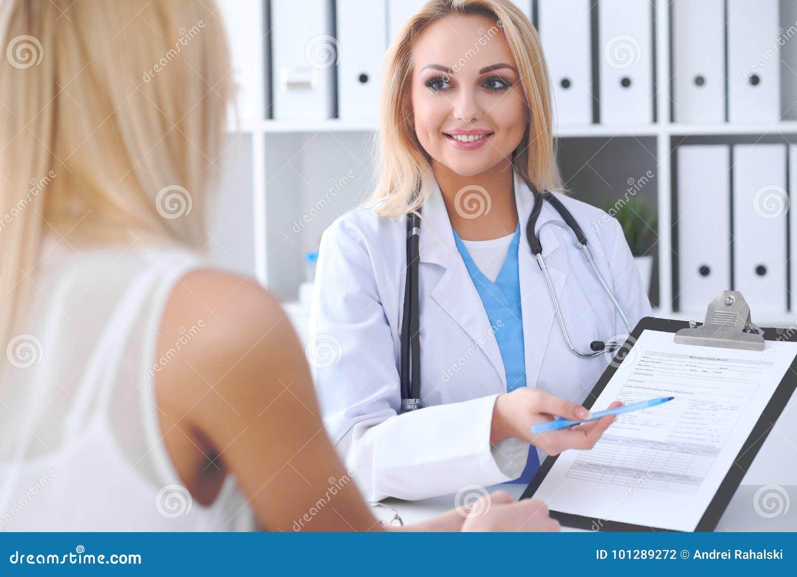 Lekarka i pacjent dyskutuje coś podczas gdy lekarz wskazuje w medycznej historii formę przy schowkiem