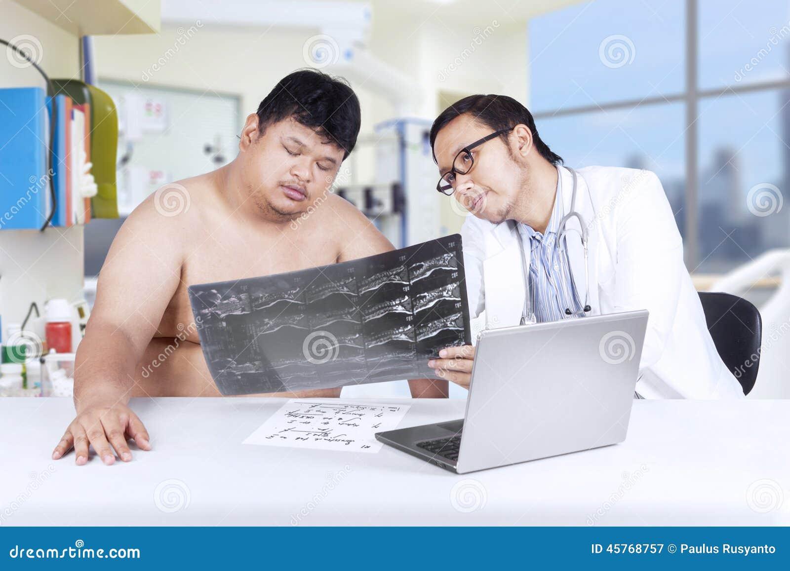 Lekarz pokazuje promieniowanie rentgenowskie z nadwagą osoba