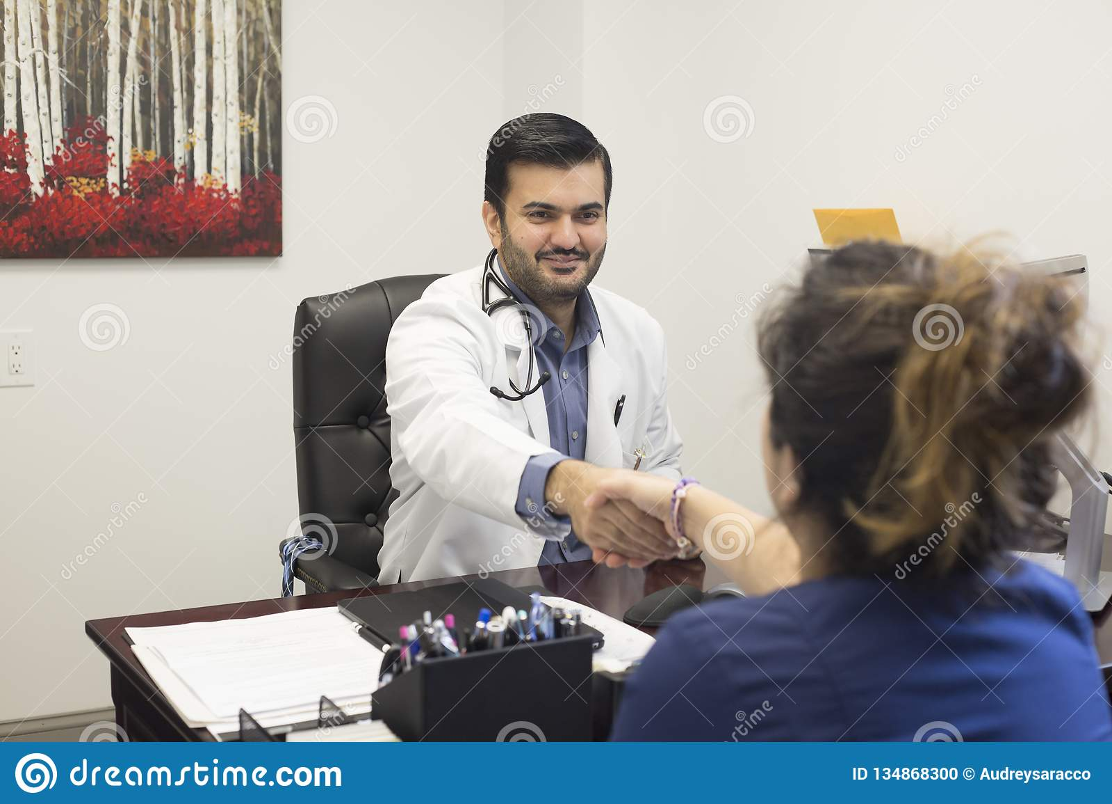 Lekarza medycynego obsiadanie przy biurkiem