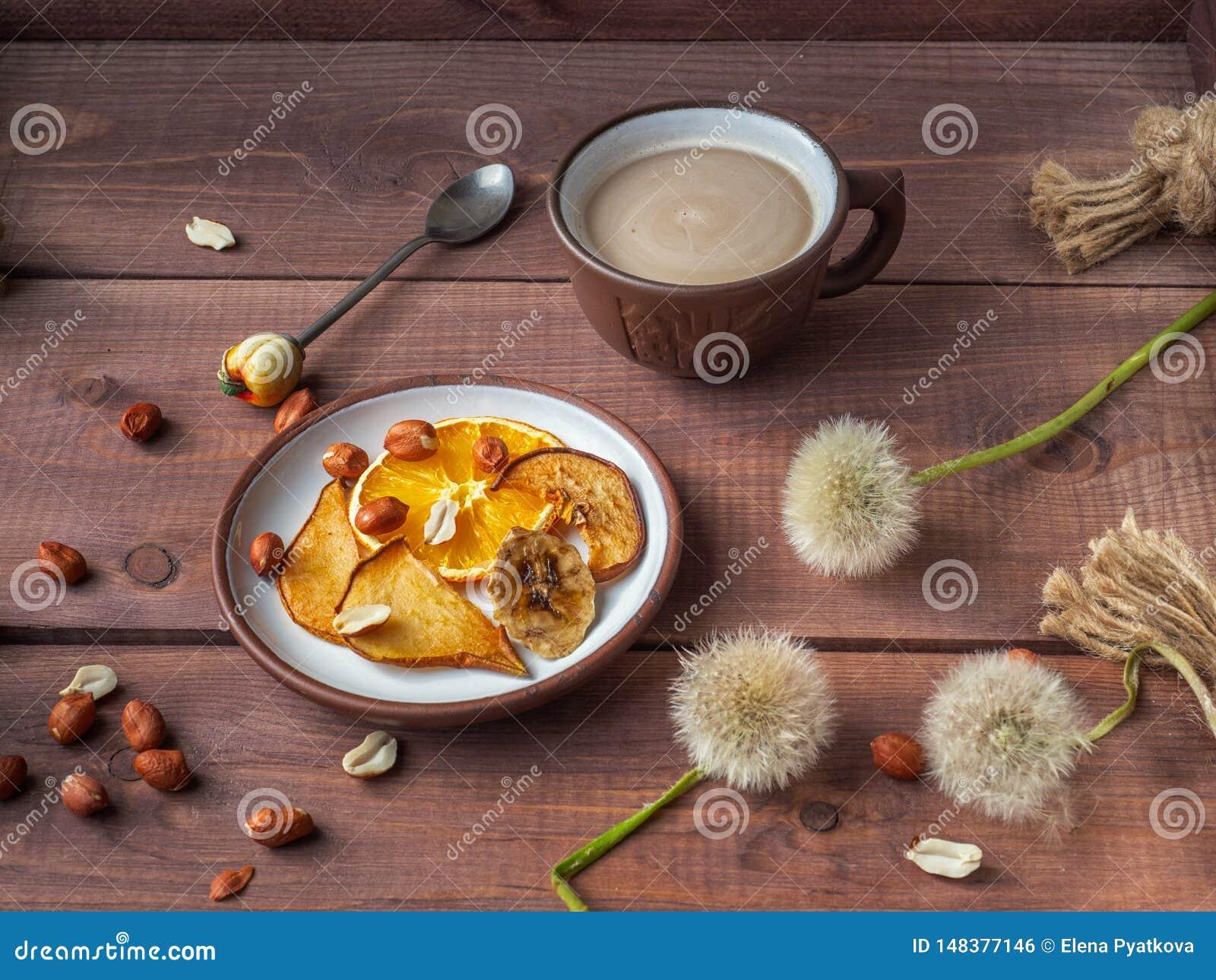 Lekcy owoc układy scaleni i arachidowe dokrętki dla lekkiej ranek kawy z mlekiem na drewnianej nieociosanej tacy