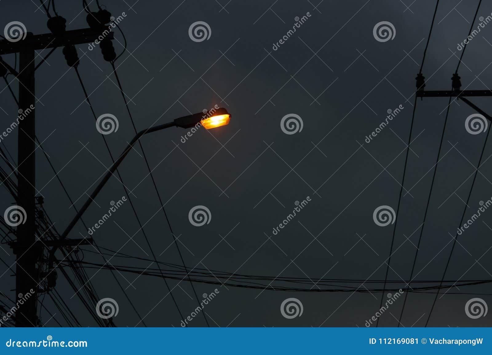 Lekka lampa na słupie z elektrycznymi drutami na ciemnym nocnego nieba backgro