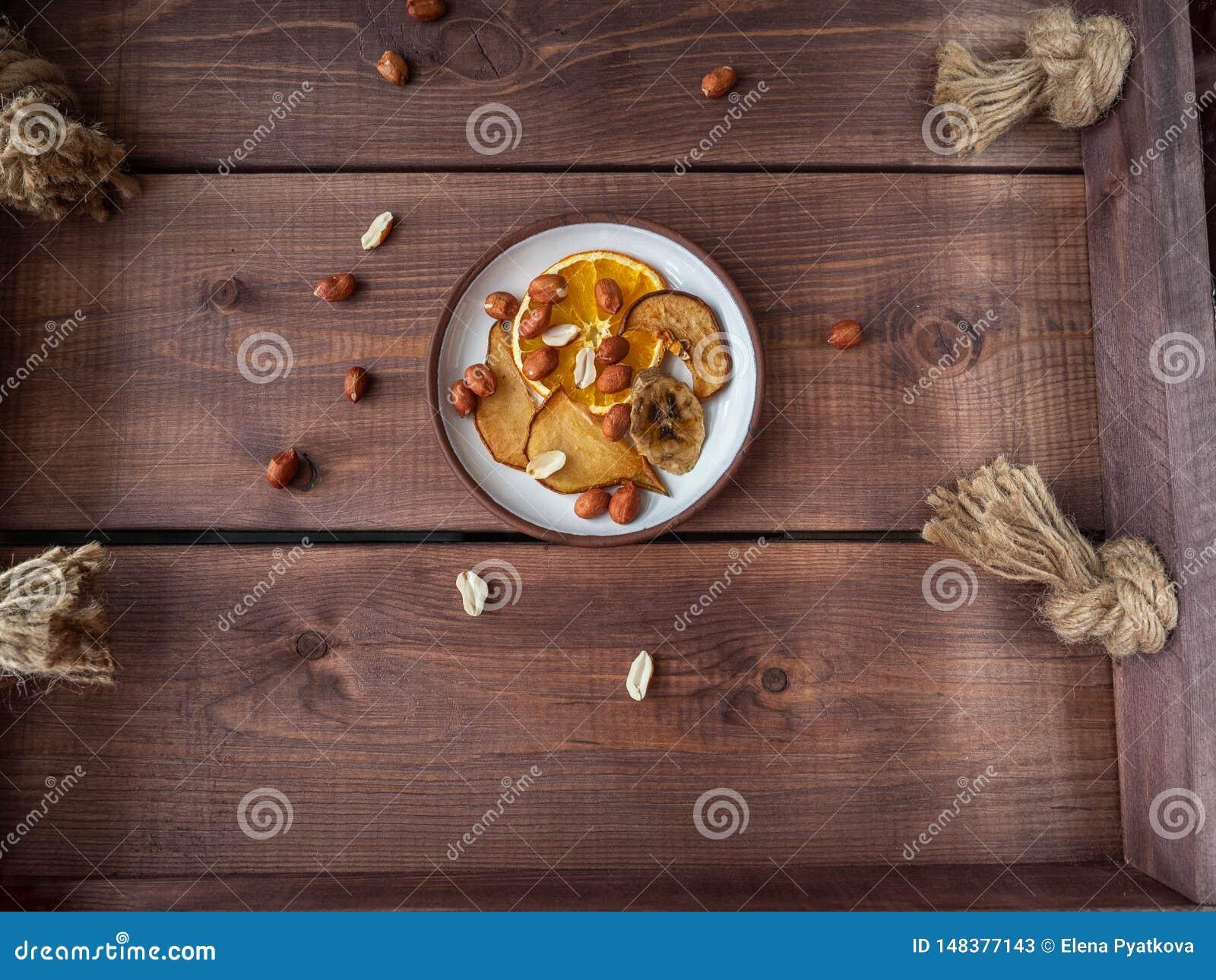 Lekka owoc szczerbi si? i arachidowe dokr?tki dla lekkiej przek?ski na drewnianej nieociosanej tacy