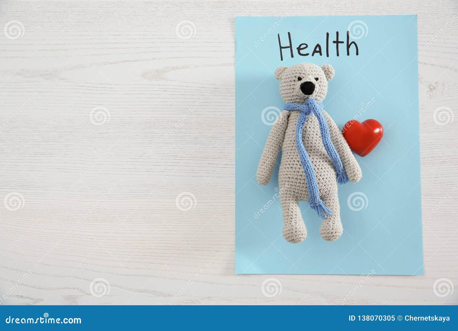Leksakbjörn, hjärta, ark av papper med ordet HÄLSA och utrymme för text på träbakgrund, bästa sikt