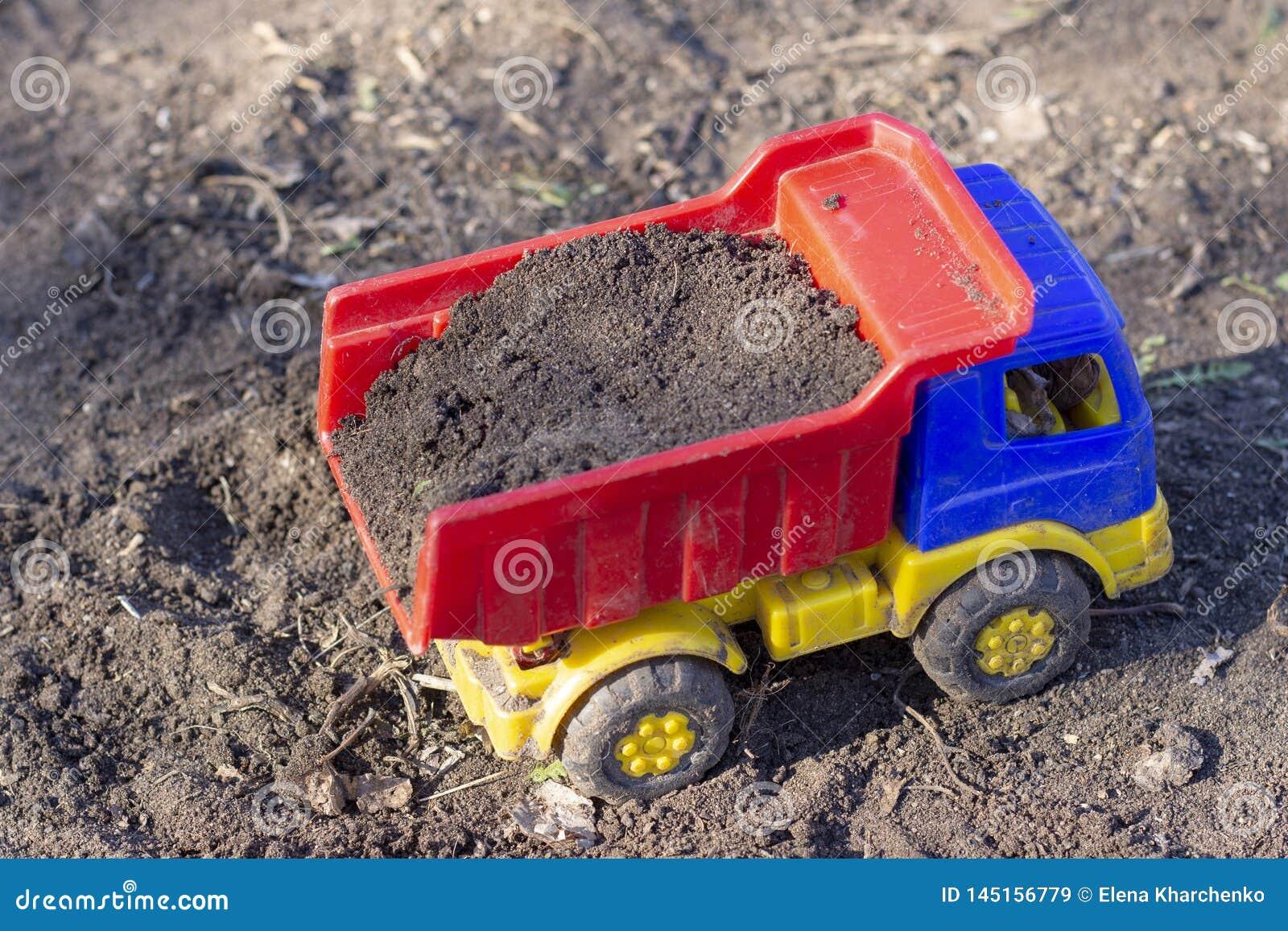 Leksakdumper står på jordningen som är full av sand
