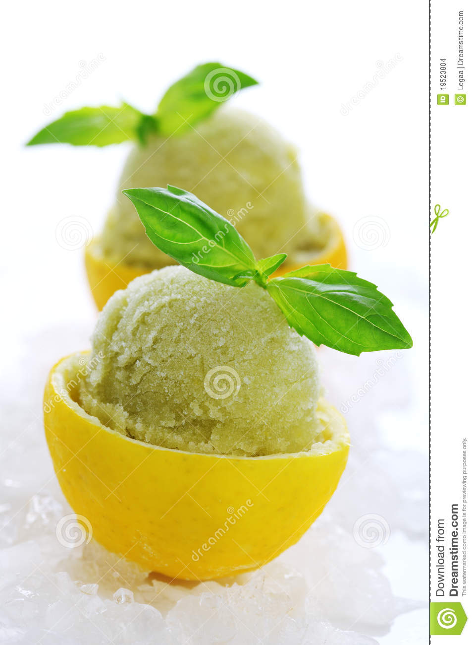 Lemon- basil sorbet in cups of lemon on white isolated background.