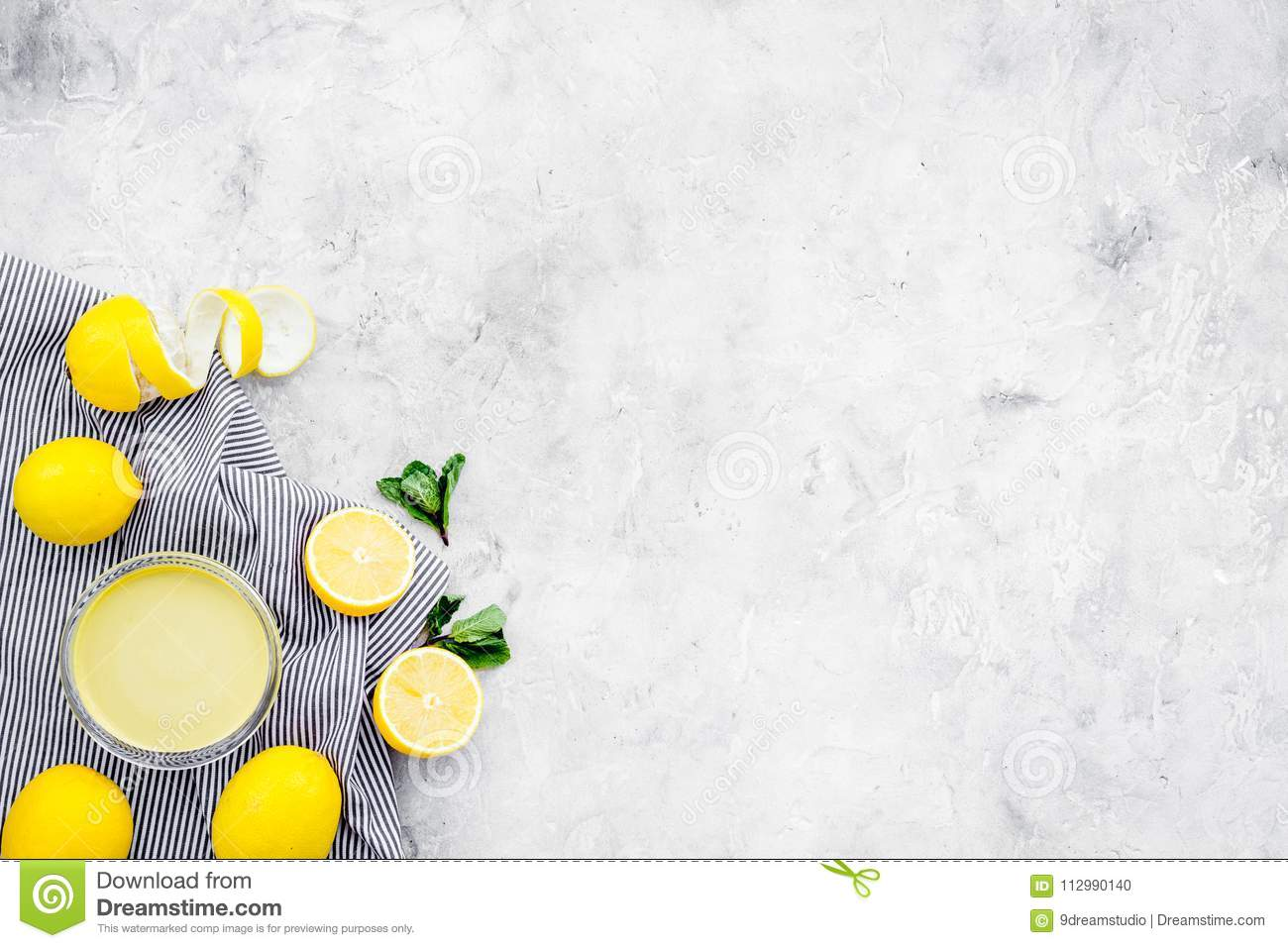 Lemon curd in bowl among lemons on grey background top view copy space