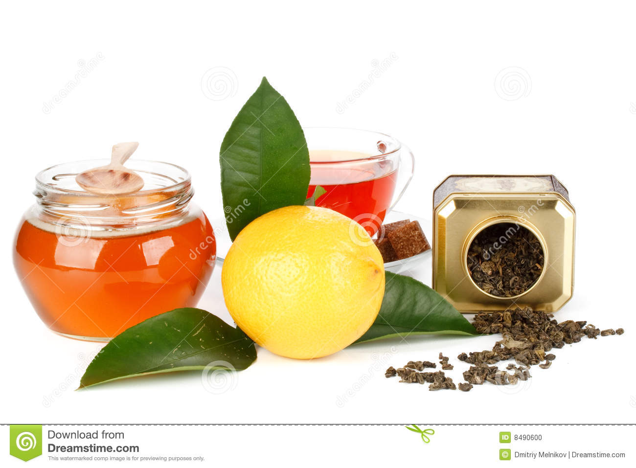 Lemon with green leaves, pot of honey and cup of tea on a white ...