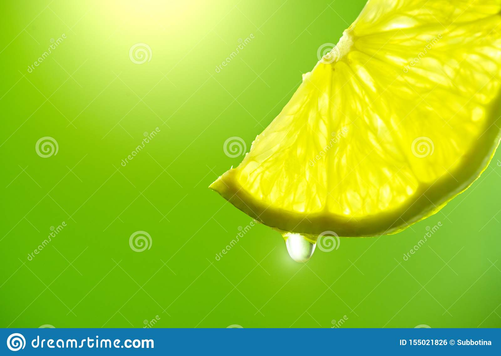 Lemon slice with drop of juice closeup. Fresh and juicy Lime over green background