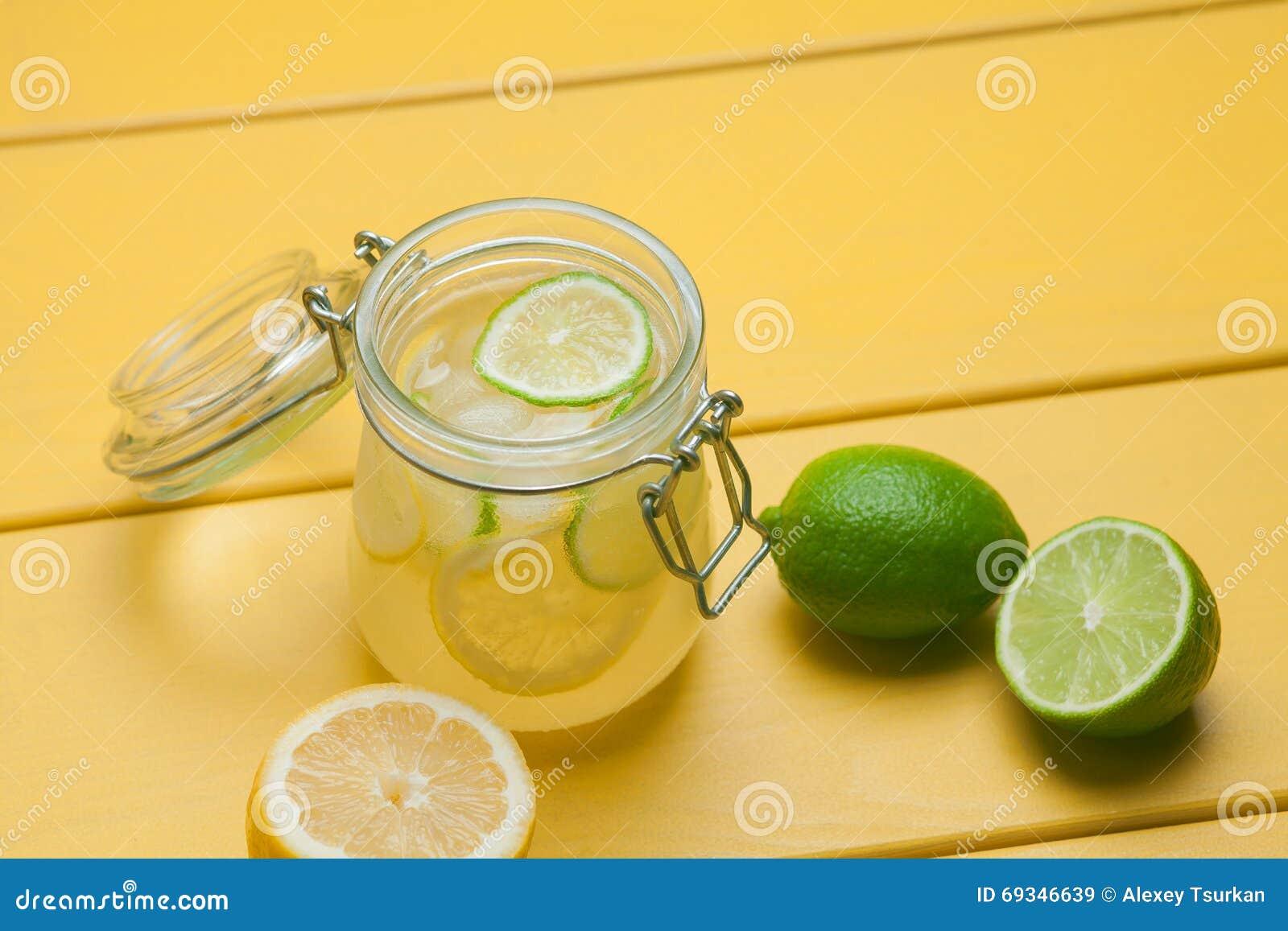 Lemonad med is, citronen och limefrukt i en krus på gula trälodisar