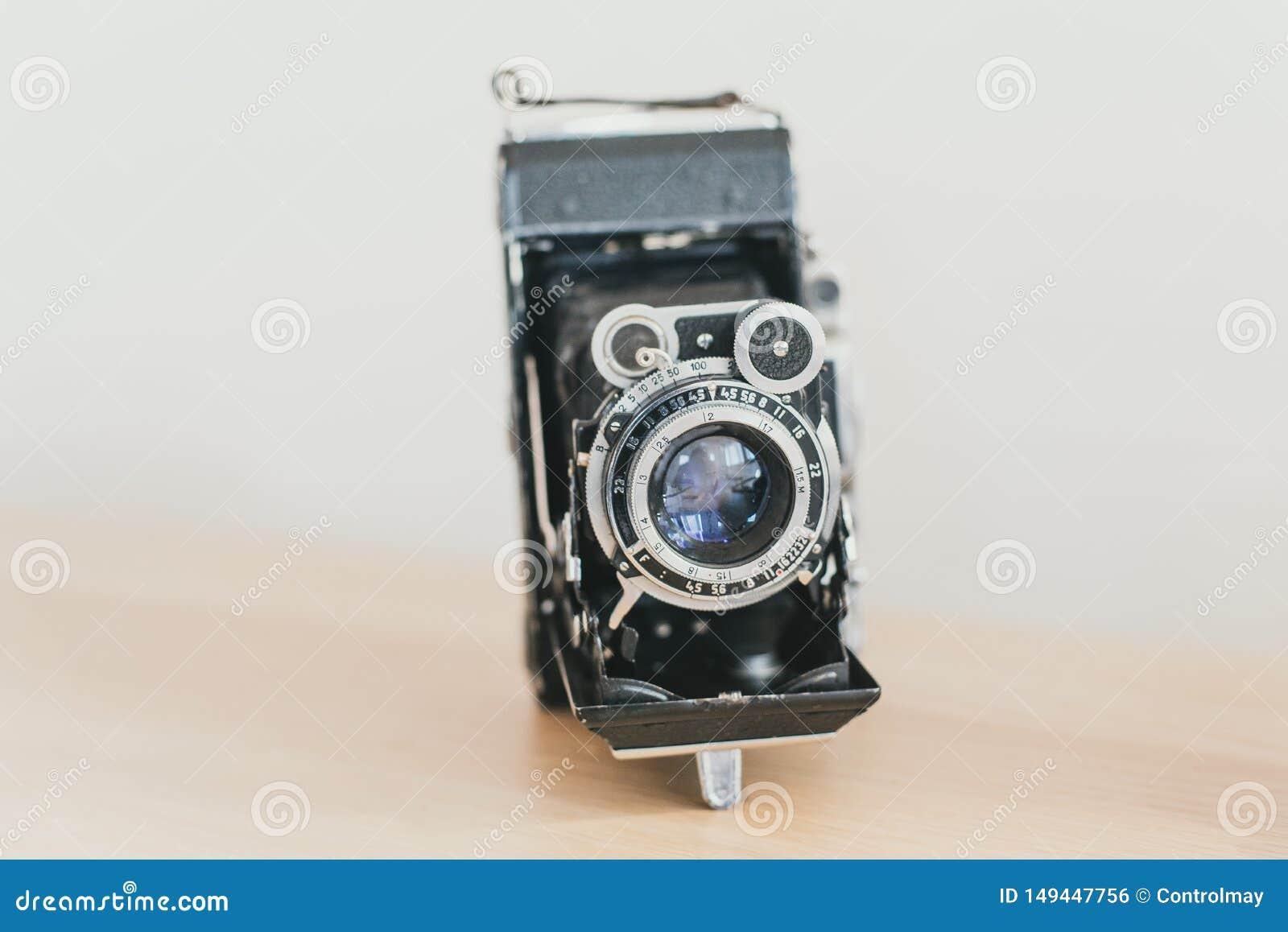 Lensharmonika op een oude camera Oude uitstekende camera op een houten lichte achtergrond